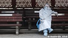 A health worker in personal protective equipment (PPE) rests before the cremation of a man who died due to the coronavirus disease (COVID-19), at a crematorium in New Delhi, India July 5, 2020. REUTERS/Adnan Abidi