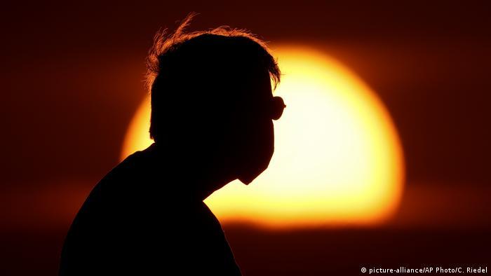 Foto de la silueta de una persona con mascarilla frente a un atardecer en Kansas