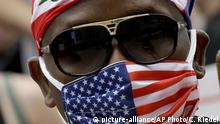 A man wears a mask as he listens to speakers in front of city hall in downtown Kansas City, Mo. Friday, June 5, 2020, during a rally to protest the death of George Floyd who died after being restrained by Minneapolis police officers on May 25. (AP Photo/Charlie Riedel) |