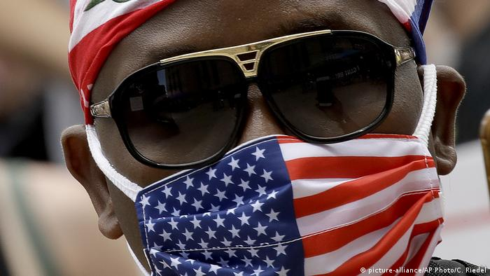 A man wears a mask as he listens to speakers in front of city hall in downtown Kansas City (picture-alliance/AP Photo/C. Riedel)