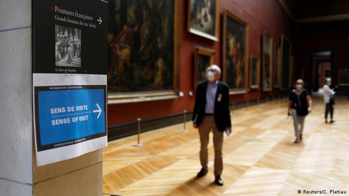 A sign indicates what direction for visitors to take at the Louve Museum in Paris as the museum partially reopens amid the coronavirus pandemic