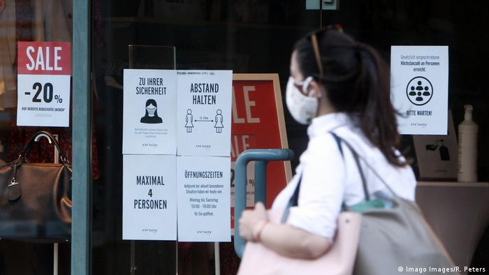 A shopper with a mask in front of shop windows with corona warnings (Imago Images/R. Peters)