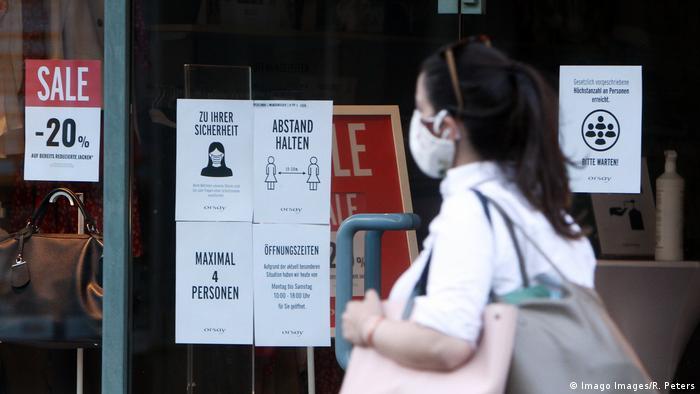 Eine Frau mit Einkaufstaschen und Nasen- und Mundschutzmaske geht an einem Gescäft mit zahlreichen Sicherheitshinweisen zur Hygiene vorbei