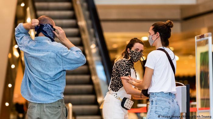 Kunden ziehen ihren Mundschutz auf und desinfizieren sich die Hände vor dem Einkaufen