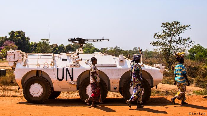 Women walk past a UN armoured vehicle in rebel-held Kaga Bandoro (Jack Losh)