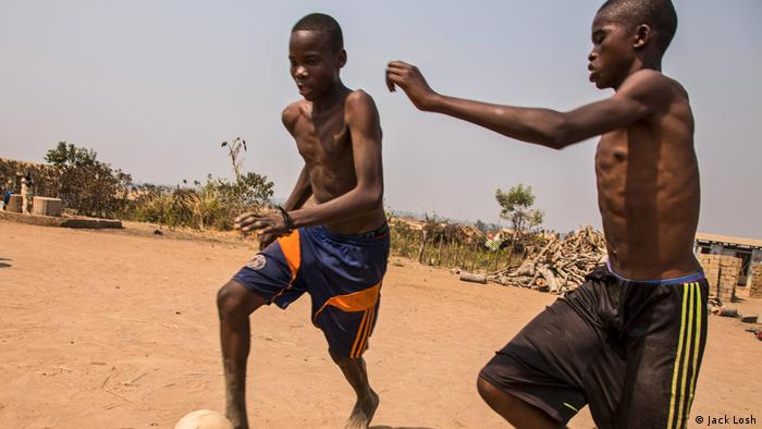 Teenage boys play football in the dust in Kaga Bandoro's displacement camp (Jack Losh)