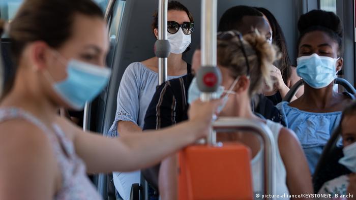 Pessoas de máscara no transporte público