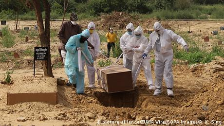 India, Grave diggers in protective gear lower a coffin into a Delhi grave (picture-alliance/ZUMA Wire/SOPA Images/A. K. Sing)