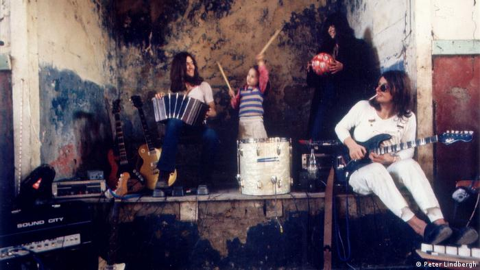 The band Neu! with a child wielding drumsticks and a woman holding an accordion on a studio stage (Peter Lindbergh)