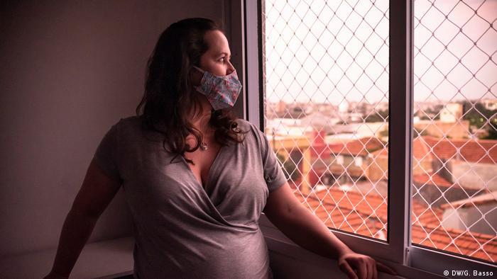 Mulher grávida de máscara diante da janela