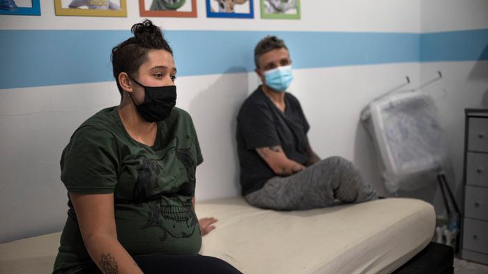 Mulher grávida de máscara ao lado de outra mulher grávida