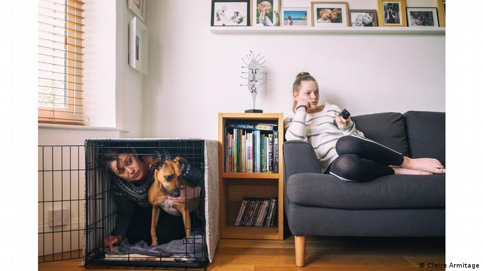 Photo from series 'There's no place like home': Woman with a dog in a dog cage; girl sitting on a sofa with a remote control in her hand (Claire Armitage)