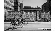 "The British Photography Awards | Cyclists wearing masks pass in front of a bank of Mark Titchner's ""Please Believe..."