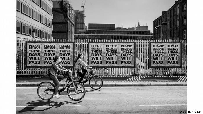 Photo from series 'When the World Stood Still': Cyclists wearing masks pass in front of a row of posters reading: 'These Days Will Pass' (Wei Jian Chan)