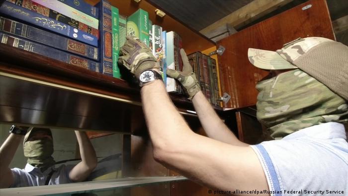 Сотрудник ФСБ проводит обыск в доме одного из крымских татар 7 июля 2020 года