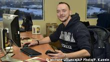 In this photo taken on Sunday Jan. 10, 2016, Ivan Safronov looks at a photographer in his working place in Kommersant Publishing House in Moscow, Russia. Safronov, an adviser to the director of Russia's state space corporation Roscosmos, has been detained on treason charges by the nation's top security agency, Tuesday July 7, 2020. (Peter Kassin, Kommersant Photo via AP)  