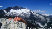 climber hands atop rock peak in Tantalus Range, Whistler, British Columbia, Canada. | Verwendung weltweit, Keine Weitergabe an Wiederverkäufer.
