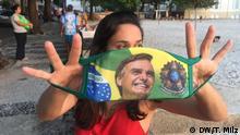 Brasilianerin hält Gesichtsmaske mit Bolsonaro-Abbild am Strand von Urca in die Kamera. Foto: Thomas Milz / DW am 7.7.2020
