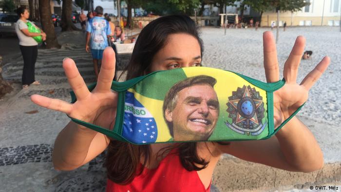 Brasilien Corona-Pandemie | Brasilianerin hält Gesichtsmaske mit Bolsonaro-Abbild in die Kamera