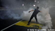 A protester trows back a tear gas canister in front of the National Assembly building in Belgrade, on July 7, 2020, as Serbian police fired tear gas to disperse thousands of protesters angry at the return of a weekend coronavirus curfew. - The crowds protested in the city centre over the government's handling of the crisis, with infections now spiking after Serbia shed its initial lockdown measures two months ago. Scuffles broke out between police and a group of protesters who stormed into the parliament building and police unleashed tear gas canisters to disperse the crowd. The demonstrators, who also lit flares and were seen throwing stones at police on local TV, chanted for President Aleksandar Vucic to Resign!. (Photo by Andrej ISAKOVIC / AFP) (Photo by ANDREJ ISAKOVIC/AFP via Getty Images)
