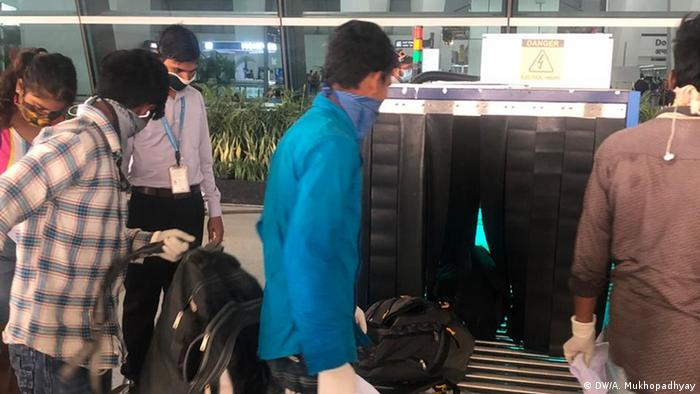 At the baggage screening people huddled close together, as officials rushed to screen bags