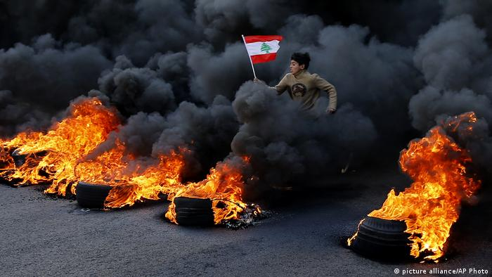 An anti-government protester in Lebanon jumps on blazing tires