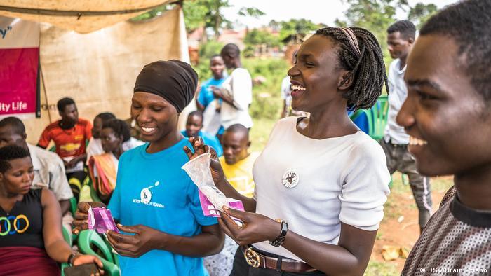 Lachelnde Frauen mit je einem Kondom in den Händen und ein Mann in Uganda: Die Deutsche Stiftung Weltbevölkerung (DSW) betreibt unter anderem in dem Land Öffentlichkeitsarbeit für Familienplanung, sexuelle Aufklärung und HIV-Vermeidung
