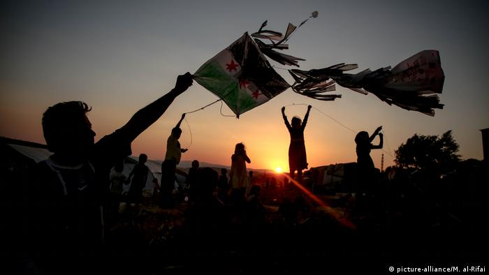 Syrian children play kites during sunset at a camp for the displaced
