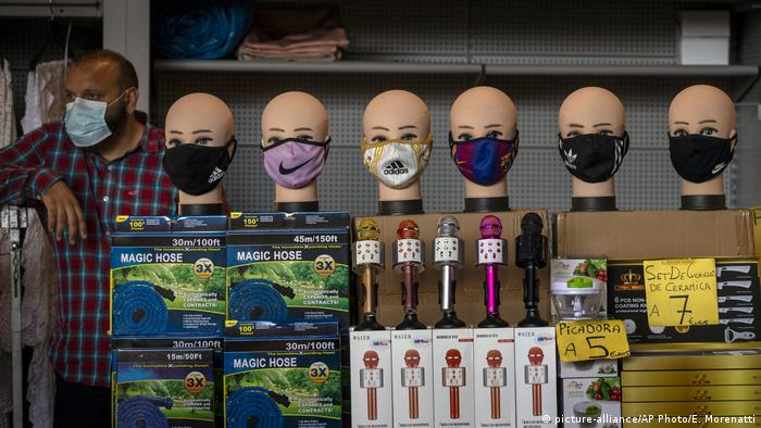 A vendor selling face masks waits for customers at a stall in a market in Barcelona