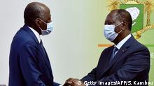 Ivory Coast Prime Minister and ruling party's candidate in the October 2020 presidential election Amadou Gon Coulibaly (L), is greeted by Ivorian President Alassane Ouattara, both wearing a protective face mask, upon his arrival at Felix Houphouet Boigny Airport after recovering in France following heart problems, in Abdijan on July 2, 2020. (Photo by SIA KAMBOU / AFP) (Photo by SIA KAMBOU/AFP via Getty Images)
