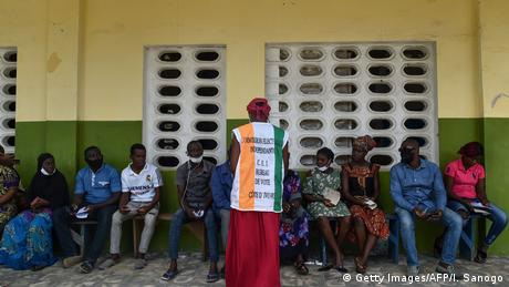 Voters waiting in queue in Ivory Coast as an election official looks on.