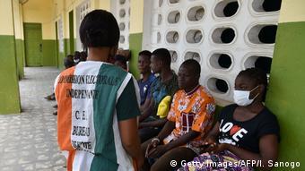 Un responsable de la Commission électorale s'occupe de personnes devant le centre d'inscription des électeurs le 4 juillet 2020, à Abidjan, à la veille de la clôture des inscriptions sur la liste électorale de la présidentielle du 31 octobre.