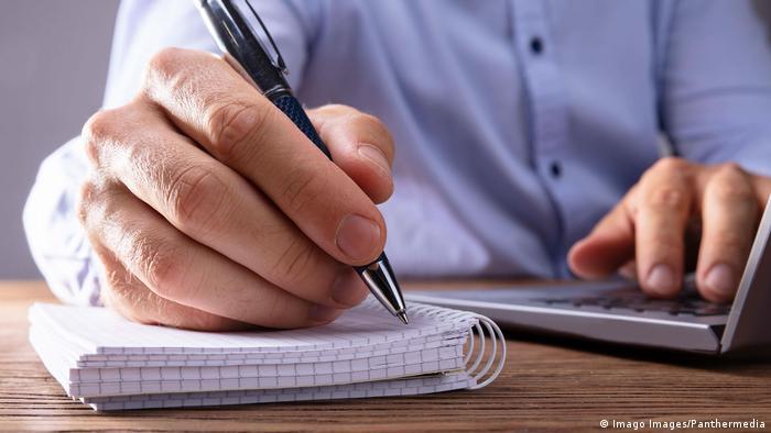 Un jurnalist care scrie intr-un carnet