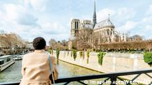 Woman looking at Notre Dame de Paris from bridge against sky, Paris, France model released (Imago Images/Westend61)