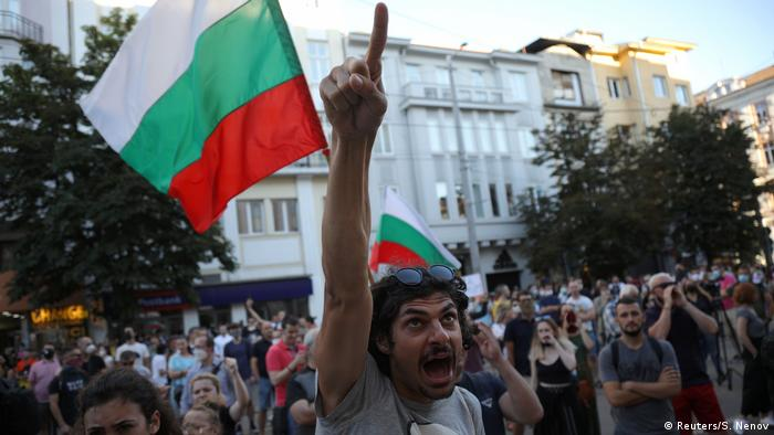 A man shouts and points his finger in front of a Bulgarian flag during demonstrations