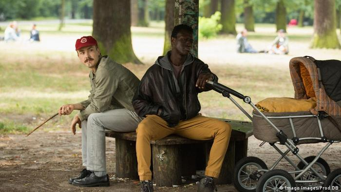 two men sit on a bench in a park, one of them, dark-skinned, overlooking a baby buggy (Imago Images/Prod.DB)