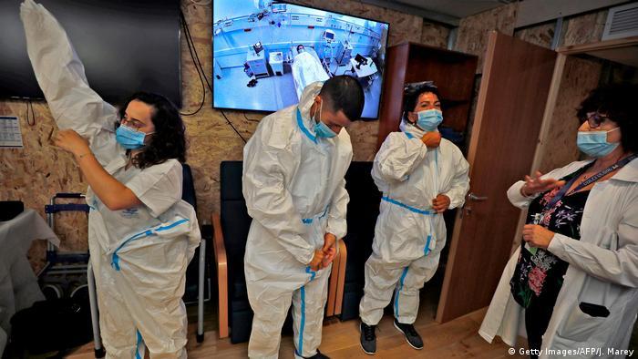 Ärzteteam in Schutzanzügen bei einer Fortbildung zur Bekämpfung des Covid-19 Virus