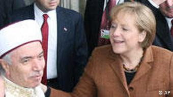 German Chancellor Angela Merkel, right, speaks with Professor Mustafa Cagrici, the Mufti of Istanbul, during her visit to the Blue Mosque, in Istanbul, Turkey, Tuesday, March 30, 2010. Turkish leaders are expected to try to break the opposition of Chancellor Merkel, during her upcoming visit, to full membership of the overwhelmingly Muslim country in the European Union. Merkel's long-standing call for Turkey to be given a privileged partnership that falls short of full membership has angered Turkish leaders. (AP Photo)