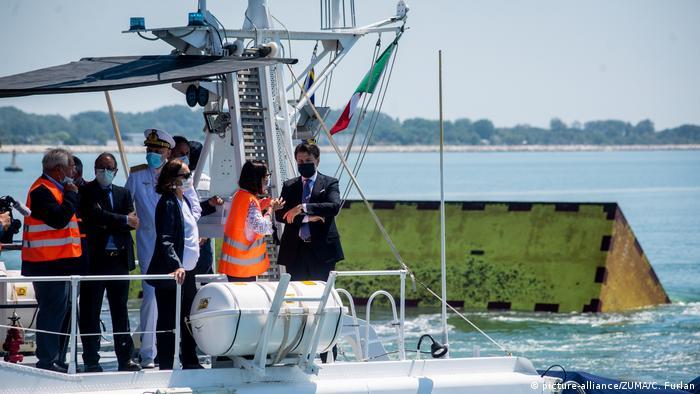 Crew on boat time rising of inflatable barriers   Schutzvorrichtung gegen Hochwasser (picture-alliance/ZUMA/C. Furlan)