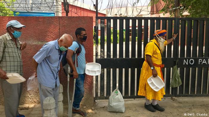 Warga New Delhi mengantre makanan untuk mengisi perut.