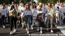 People march dressed in white, family members hold photo of Monguillot and wife | Trauer um getöteten Busfahrer | Ehefrau (picture-alliance/NurPhoto/J. Gilles)