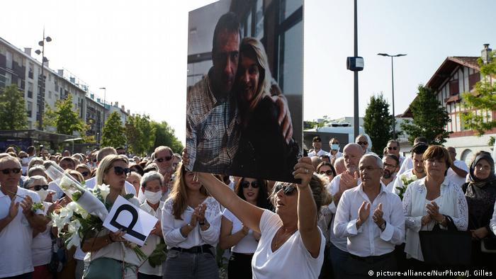 Philippe Monguillot's wife holds up photo of the pair at the march (picture-alliance/NurPhoto/J. Gilles)