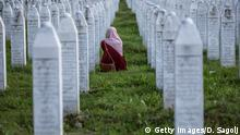 10.07.2020 SREBRENICA, BOSNIA AND HERCEGOVINA - JULY 10: A Bosnian Muslim woman cries between graves of her father, two grandfathers and other close relatives, all victims of Srebrenica genocide, July 10, 2020, at the cemetery in Potocari near Srebrenica, Bosnia and Hercegovina. More than 8,000 Bosnian Muslim men and boys were killed after the Bosnian Serb Army attacked Srebrenica, a designated UN safe area, on 10-11 July 1995, despite the presence of UN peacekeepers. There have been high-level prosecutions of some principal architects of the war in Bosnia and Herzegovina, including Ratko Mladic and Radovan Karadzic, yet there is still a backlog of cases pending before courts in the country. (Photo by Damir Sagolj/Getty Images)