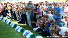 People pray near coffins at a graveyard during a mass funeral in Potocari near Srebrenica, Bosnia and Herzegovina July 11, 2020. Bosnia marks the 25th anniversary of the massacre of more than 8,000 Bosnian Muslim men and boys, with many relatives unable to attend due to the coronavirus disease (COVID-19) outbreak. REUTERS/Dado Ruvic