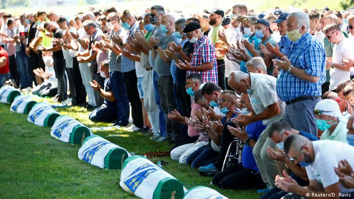 People praying in front of coffins