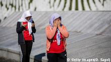 """SREBRENICA, BOSNIA AND HERCEGOVINA - JULY 10: Bosnian Muslim women pray as they visit the cemetery for victims of Srebrenica genocide, July 10, 2020, in Potocari near Srebrenica, Bosnia and Hercegovina. More than 8,000 Bosnian Muslim men and boys were killed after the Bosnian Serb Army attacked Srebrenica, a designated UN """"safe area"""", on 10-11 July 1995, despite the presence of UN peacekeepers. There have been high-level prosecutions of some principal architects of the war in Bosnia and Herzegovina, including Ratko Mladic and Radovan Karadzic, yet there is still a backlog of cases pending before courts in the country. (Photo by Damir Sagolj/Getty Images)"""