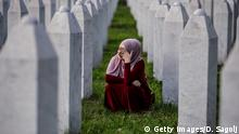 SREBRENICA, BOSNIA AND HERCEGOVINA - JULY 10: A Bosnian Muslim woman cries between graves of her father, two grandfathers and other close relatives, all victims of Srebrenica genocide, July 10, 2020, at the cemetery in Potocari near Srebrenica, Bosnia and Hercegovina. More than 8,000 Bosnian Muslim men and boys were killed after the Bosnian Serb Army attacked Srebrenica, a designated UN safe area, on 10-11 July 1995, despite the presence of UN peacekeepers. There have been high-level prosecutions of some principal architects of the war in Bosnia and Herzegovina, including Ratko Mladic and Radovan Karadzic, yet there is still a backlog of cases pending before courts in the country. (Photo by Damir Sagolj/Getty Images)