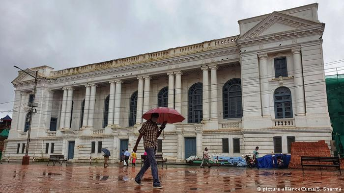 A man walks in front of the Gaddi Baithak Palace in Kathmandu, Nepal as rains lash the country