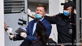 Полицейские заводят Сергея Фургала в автозак
