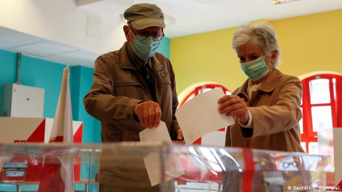 Voters wearing face masks cast their ballots during the second round of presidential election at a polling station in Warsaw (Reuters/A. Szmigiel)